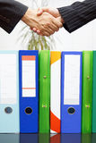 Woman and man are handshaking over binders, handing business con Stock Images