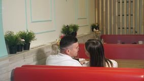 Woman and man have date sitting on red sofa in cozy cafe. Happy young woman and man have romantic date sitting on red sofa at table in modern cozy cafe backside stock video footage