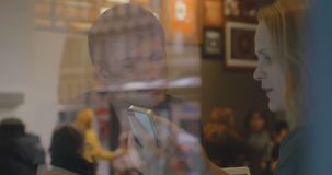Woman and man have a discussion in the restaurant. View through restaurant glass of woman and man talking cheerfully, woman shows something on the smartphone stock footage
