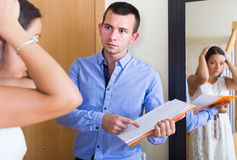 Woman and man having argue with documents at doorway Stock Photos