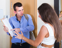 Woman and man having argue with documents at doorway Royalty Free Stock Image