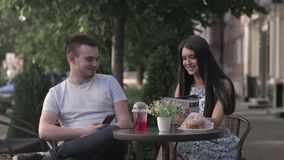 A woman and a man are having a conversation in a summer cafe. Young happy couple chatting in cafe stock footage