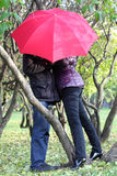 Woman and man hide behind red umbrella in park Stock Photos