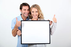 Woman and man holding board Stock Image