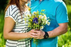 Woman and man holding hands, girl with bouquet of chamomile, love concept.Couple in love.Date.Loving couple are holding stock photography