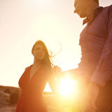 Woman and man holding hands on sunrise. Young couple holding hands on sunrise backlit Stock Photos