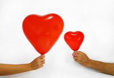 A woman and a man are holding heart-shaped balloons in their hands. Valentine`s day. Valentine`s day. A woman and a man are holding heart-shaped balloons in stock images