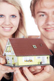Woman and man holding a miniature house Royalty Free Stock Image