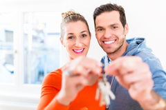 Woman and man holding proudly home or house key Royalty Free Stock Photos
