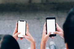 Woman and man holding a smartphone, mock up of blank screen. using cell phone on lifestyle. Technology for communication concept royalty free stock image