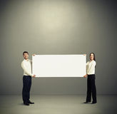 Woman and man holding white banner Royalty Free Stock Photography