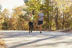 Woman and man jogging on a country road, mid distance Stock Photo