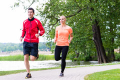 Woman and man jogging on dirt path in the woods together Stock Photos