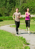 Woman and man jogging in park Stock Photo