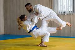 Woman and man judo fighters in sport hall. Young women and men judo fighters in sport hall stock photo