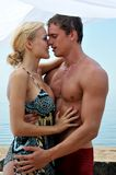 Woman and man kissing at the beach. Stock Photos