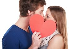 Woman and man kissing behind red heart Stock Images