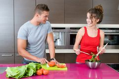 Woman and man in the kitchen with salad Royalty Free Stock Images