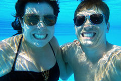 A woman and a man laugh underwater in the pool Stock Photo