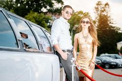 Woman and man leaning against a limo car stock images