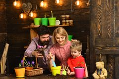 Woman, man and little boy child love nature. happy gardeners with spring flowers. Flower care watering. Soil fertilizers. Woman, men and little boy child love royalty free stock photos