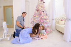 Woman, man and little girl hand Christmas presents its half in s. Young parents happy husband and wife with douther take out from under Christmas tree with gift Stock Image