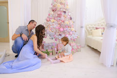 Woman, man and little girl hand Christmas presents its half in s. Young parents happy husband and wife with douther take out from under Christmas tree with gift Stock Photography