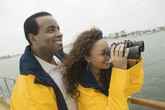 Woman With Man Looking Through Binoculars Royalty Free Stock Images