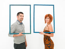 Woman and man looking through empty frames Stock Image