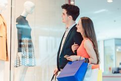 Woman and man looking at fashion shop window Stock Images