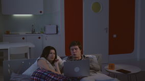 Woman and man lying on bed watching video. stock video