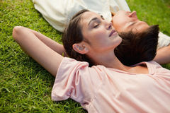 Woman and a man lying head to shoulder Stock Photos