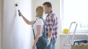 Woman and man makes repairs. Young family makes repairs in new flat. Beautiful couple - painting wall in apartment. Man and woman doing overhaul of house. Guy stock footage