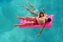 Woman and the man on a mattress. Young woman and the man on a mattress in water pool Stock Photo