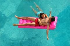 Woman and the man on a mattress in pool. Young woman and the man on a mattress in pool Royalty Free Stock Photo