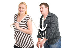 Woman and man metaphor. Pregnant woman restricting man's freedom with a rope and anchor isolated on white background Stock Images