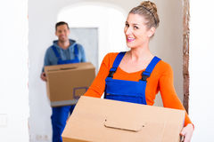 Woman and man moving in new home with boxes Stock Photo