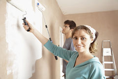 Woman And Man Painting Wall With Paint Rollers Stock Photography