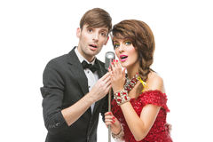 Woman and man performing song in retro microphone. Beautiful young couple in festive clothes singing into retro microphone. Isolated over white background. Copy Stock Photography