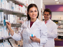 Woman and man pharmacists at the chemists shop. Pharmacist women in a white coat at the chemists shop royalty free stock photography