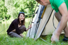 Woman and man pitching a tent Stock Photos