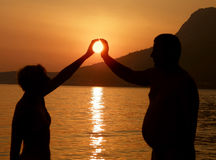 Woman and man play with sun. Attractive woman and big man take a sun in hands Stock Photo