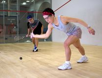Woman and man playing squash stock photography