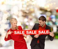 Woman and man pointing finger to red sale sign Royalty Free Stock Photo