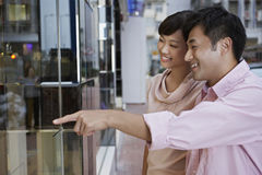 Woman With Man Pointing At Window Display Royalty Free Stock Images