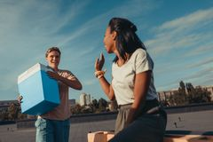 Woman and man with portable fridge. Happy women and men with portable fridge on roof Royalty Free Stock Photography
