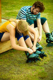 Woman and man putting on roller skates Royalty Free Stock Photography