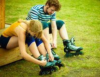 Woman and man putting on roller skates Stock Photography