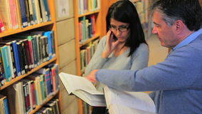 Woman and man reading books in the library stock footage