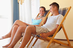 Woman and man reclining on chaise lounges in hotel. Young smiling woman and man reclining on chaise lounges in hotel room on resort stock photography